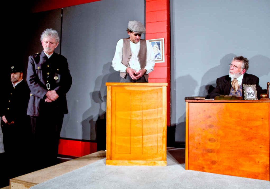 Warder O'Donnell (Kelvin Willis), Constable McCluskey (Michael Kennedy), George McCauley (Ron Thomas) in the dock, and the Magistrate (Barry Magowan)